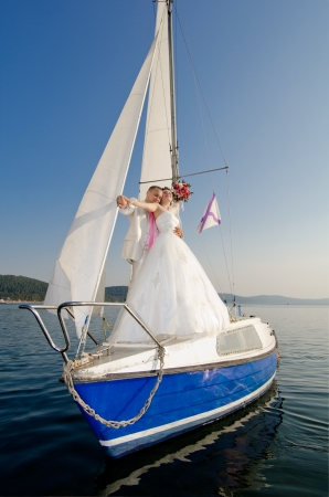 vertical photo  newly married couple stand on  white yacht, outdoor Stock Photo - 15395315