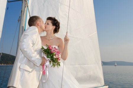 vertical photo  newly married couple stand on  white yacht, outdoor Stock fotó