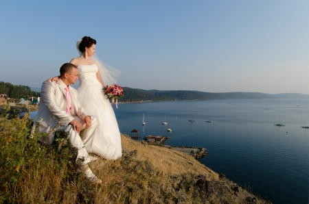 happy newly married couple on background of beauty sea  landscape  on sunset