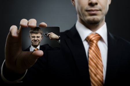 sorrowfully: businessman in black costume and orange necktie reach out on camera and show credit card or visiting card, close up