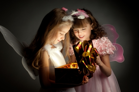 fancy box: two little girl examine gift in fancy box, smile, on dark background