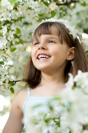 portrait  beautiful little girl, with bush blossoming apple-tree, smiles photo