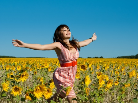 quickly: The young beautiful woman quickly runs on a glade of sunflower, smiles, hands are opened  Stock Photo