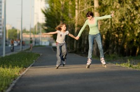 niños caminando: Madre con la hija ir en patines, al aire libre, en la noche de verano