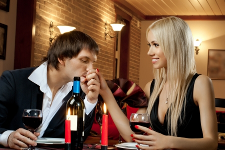 romantic evening date in hotel room, or supper in restaurant, happy couple with wine glass photo