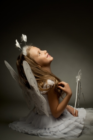 angel alone: beautiful  little girl with wings, sit and  smile on dark background
