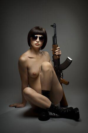 girl sexy nude: sensualidad hermosa chica sexy desnuda con metralleta, en el fondo oscuro luz glamour, Foto de archivo
