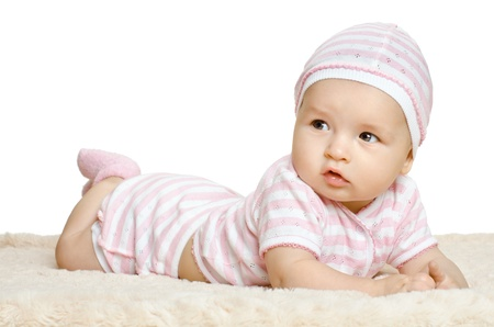 the very  beautiful  little baby  in pink dress, lie on stomach,  on white background, isolated photo