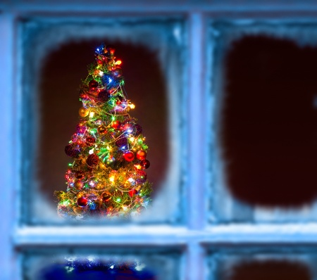 beautiful Christmas firtree with resplendent multicoloured garland , through wintry frozen window Stock Photo - 15719093