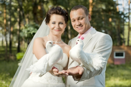 Happy newly married couple with two white  pigeon, smile
