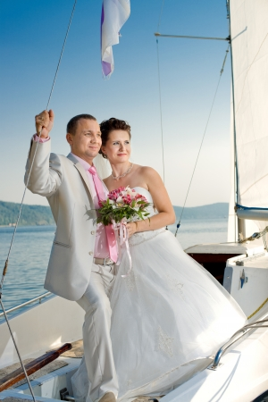 Newly married couple stand on  white yacht, outdoor Stock Photo