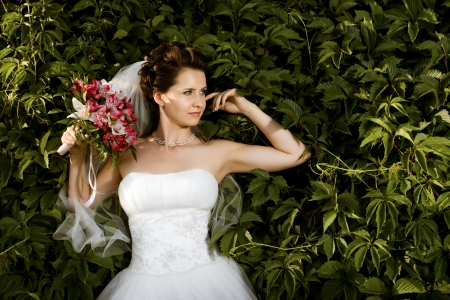 fiancee: Beautiful  fiancee with  bouquet  in white dress, soft light Stock Photo