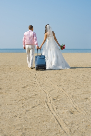 happy newly married couple to go  on a honeymoon ,  on  sea  Stock Photo - 15719079