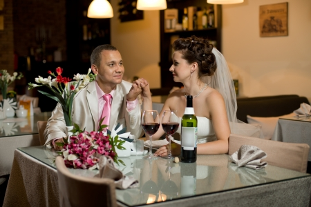 newly married couple sit at table in restaurant,  romance wedding dinner Фото со стока