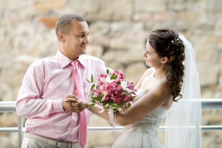 atilde: happy newly married couple ,  outdoor, focus on  wedding bouquet