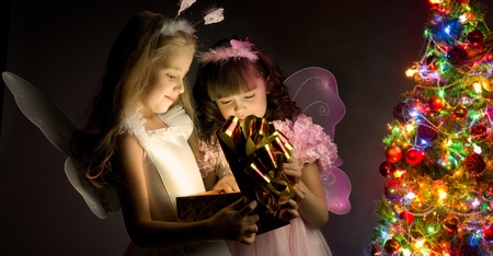 lambent: two little girl examine gift in fancy box, smile, on dark background with  Christmas-firtree