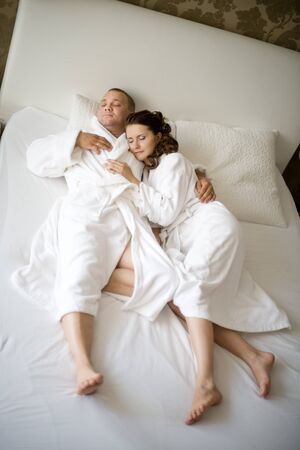 bedstead: happy couple lie together in  bedstead on white bed,   sleep and embrace