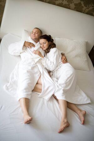pareja durmiendo: pareja feliz yacen juntos en cama en cama blanca, dormir y abrazar Foto de archivo