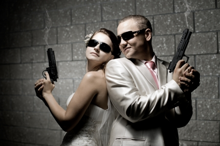 newly married couple in white wedding dress, shoot of  black pistols photo