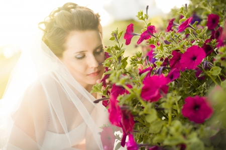 fiancee: horizontal wedding portrait beautiful  fiancee smelled  beauty flowerbed of red-lilac-coloured flowers,  outdoor