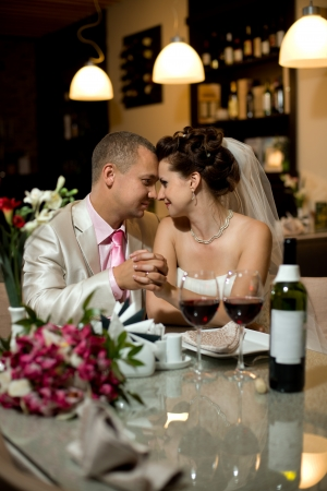 merriment: newly married couple sit at table in restaurant,  romance wedding dinner Stock Photo