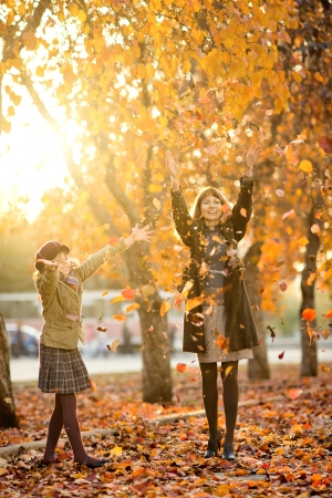 leafage:   happy beautiful little girl with mother throw up  autumnal leafage, in park. Focus on little girl. Stock Photo