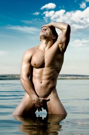 uomo nudo: il bel ragazzo molto muscoloso sexy su sfondo cielo e mare
