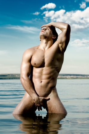 nude outdoors: the very muscular handsome sexy guy on sky and sea background