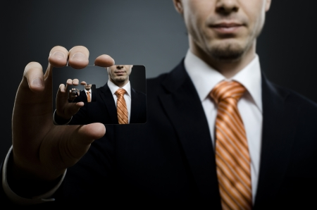 businesscard: businessman in black costume and orange necktie reach out on camera and show credit card , close up