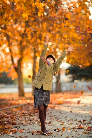 fling: vertical photo,  happy beautiful little girl joyful  laughter throw up  autumnal leafage, in park