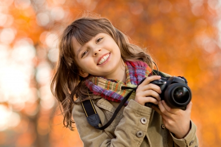 cameraman: horizontal photo, happy beautiful little girl with photocamera, autumnal portrait Stock Photo