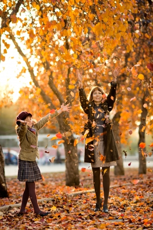 leafage: Vertical photo,  happy beautiful little girl with mather throw up  autumnal leafage, in park  Focus on little girl