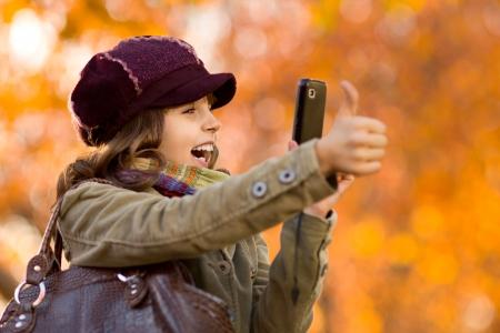 telephony: horizontal photo, happy beautiful little girl take a photograph on  mobile phone, autumnal portrait Stock Photo