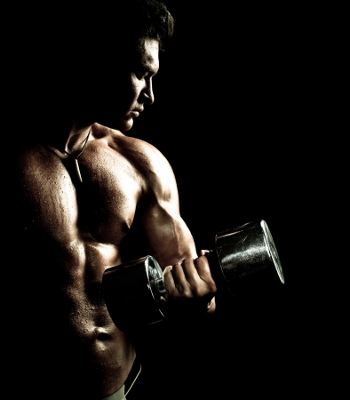 tough man: very power athletic guy ,  execute exercise with  dumbbells, on bkack background Stock Photo