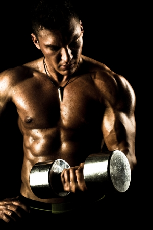 very power athletic guy ,  execute exercise with  dumbbells, on bkack background Stock Photo