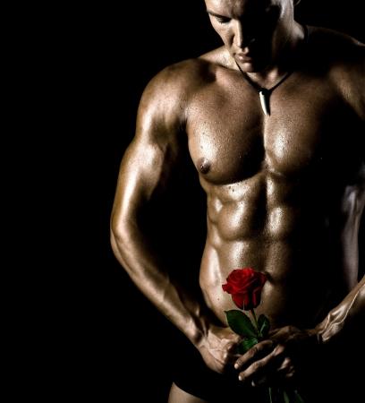 uomini nudi: il bel ragazzo molto muscoloso sexy su sfondo nero, il torso nudo