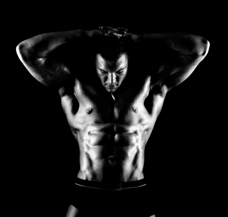 the very muscular handsome sexy guy on black background, naked  torso,  black-and-white