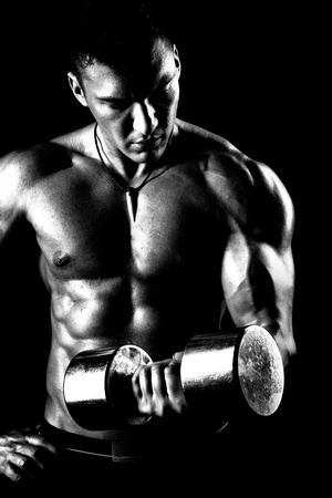 very power athletic guy ,  execute exercise with  dumbbells, on bkack background, black-and-white Stock Photo - 16191629