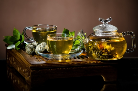 trivet: horizontal  picture  still life of the glass teapot with green tea and two cup on  wooden trivet Stock Photo