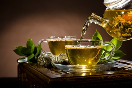 tea ceremony: horizontal picture, of the glass teapot flow green tea in cup on brown background,  tea ceremony Stock Photo