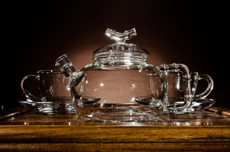 trivet: horizontal picture of the glass teapot with  cup on  wooden trivet, on dark background