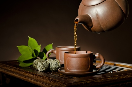 tea set: horizontal picture, of the clay teapot tea flow in  cup on brown background,  tea ceremony