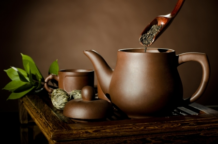 tea set: horizontal picture, tea pour in clay teapot,   on brown background,  tea ceremony Stock Photo