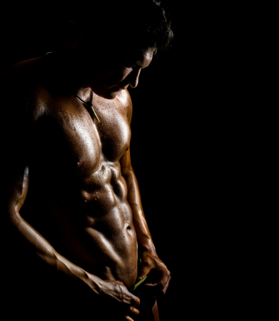 undressed: the very muscular handsome sexy guy on black background, naked  torso