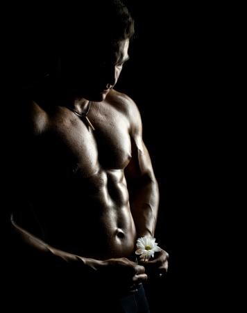 naked man: la muy musculoso chico guapo sexy con flor sobre fondo negro, torso desnudo Foto de archivo
