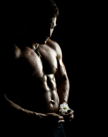 the very muscular handsome sexy guy with flower on black background, naked  torso Stock Photo - 16711217