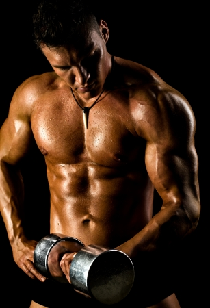 musculation: very power athletic guy ,  execute exercise with  dumbbells, on black background Stock Photo
