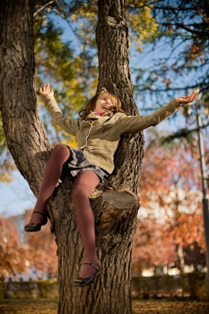 belle: vertical photo,  happy beautiful little girl sit on tree and joyful  laughter , in autumnal park