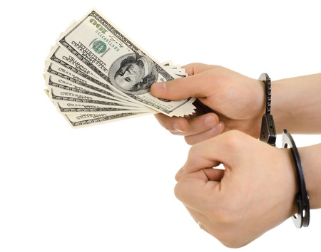 subornation: hand in shackle hold  currency note dollars, on white background, isolated Stock Photo