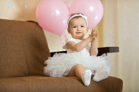 the happy little baby girl in white dress smile , sit on sofa indoor Stock Photo - 17203871
